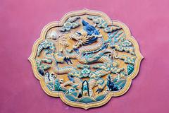 Carved dragon on the red wall of Forbidden City Stock Photos