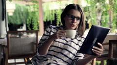 Woman reading news on tablet computer and drinking coffee in cafe HD Stock Footage