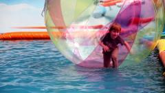 Young boy kids in zorb bubble ball swimming in pool - stock footage
