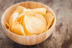 Crispy potato chips on wooden background Stock Photos