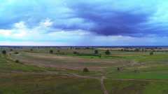 Flight in  field and storm clouds with  rain on a distance shot.Aerial Stock Footage