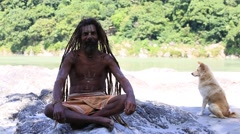 Stock Video Footage of Sadhu man and dog sits on the ghat along the Ganges river. Rishikesh, India