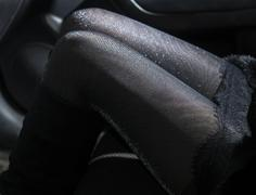 Slender sexy legs in shiny pantyhose in car - stock photo