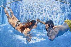 Positive couple swimming underwater in outdoor pool Stock Photos