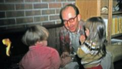 1973: Grandpa teaching the kids about fireplace safety. Stock Footage