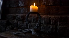 Candle burning against stone backdrop- hand held shot Stock Footage