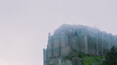 Old stone monastery standing on high hill hidden in fog. Ancient architecture Stock Footage