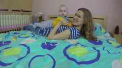 Loving woman and 5 month old baby girl laugh and play on bed. 4K Stock Footage