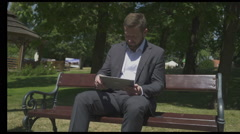 Busienessman browsing tablet sitting on wooden bench in park. Stock Footage