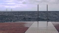 Waves splashing wooden ocean pier on stormy day Stock Footage