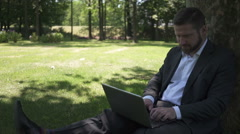 Businessman finishes work on laptop, sitting under tree in park. Stock Footage