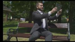 Businessman takes selfie by tablet, sitting on wooden bench in park. Stock Footage