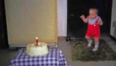 1973: One year old awkwardly walks to birthday party cake and burns himself on - stock footage