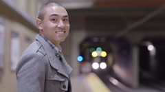 Asian Man Smiles At Camera, Then Turns To Look At Approaching Train (4K) Stock Footage