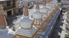 Budhist man spinning prayer wheels around chorten,Kaza,Spiti,India Stock Footage