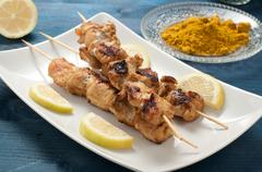 Indonesian chicken satay skewers with curry , peanut butter and soy sauce - stock photo