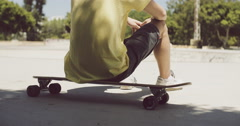 Man sitting on his longboard at a skate park Stock Footage