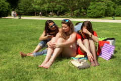 Friends sitting in the park and talking on loudspeaker, steadycam shot Stock Footage