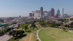 Aerial Dallas skyline & Griggs park & highway traffic- camera flies backwards Stock Footage