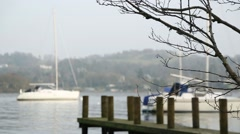 Boats moored on calm waters at Lake Windermere, focus foreground - stock footage