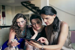 Girlfriends sitting on the sofa and browsing internet on tablet, steadycam shot Stock Footage