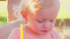 Cute blonde toddler outside in the sun - stock footage