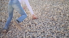 Back of girl in jeans crawling on gravel pile at sunny day Stock Footage