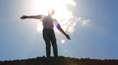 Girl jumps on stone pile and depicts bird during sunny day Stock Footage