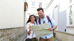 Couple of tourists in the street reading map and going away Stock Footage