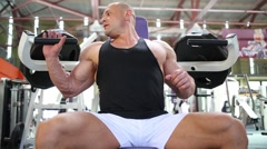 Bodybuilder in jersey trains on simulator in gym hall Stock Footage