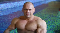 Bodybuilder strains muscles in water of indoor pure pool Stock Footage