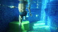Legs of man rising stairs under water of pool with blue tiles Stock Footage