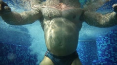 Man falls under water of pool with bubbles and strains muscles - stock footage