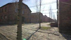 Buildings behind the barbed wire fence at Auschwitz Stock Footage