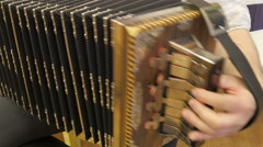 A man playing an accordion while sitting Stock Footage