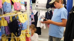 Boy and girl choose clothes in supermarket Moskovsky Stock Footage