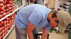 Boy in cap adds purchases in cart in clothes supermarket Stock Footage