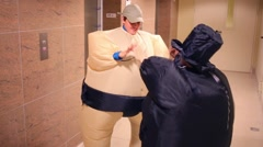 Boy and girl in inflatable costumes fight next to elevator Stock Footage