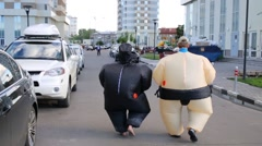 Back of boy and girl in inflatable costumes going near buildings Stock Footage