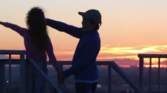 Back of boy and girl looking sunset and pointing by fingers Stock Footage