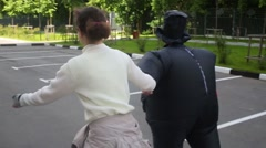 Back of woman and girl in inflatable costume ride on roller skates Stock Footage