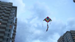 Colorful kite flies in sky on wind among residential buildings Stock Footage