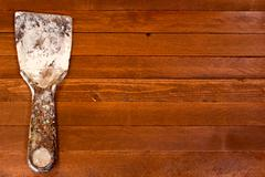 Rusty dirty spatula scraper toolon a brown wooden background. Copy space to r Stock Photos