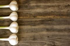 Fresh garlic bulbs with long stalk on wood table with copy space Stock Photos
