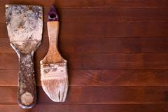 Soiled in a paint brush on unpainted natural wooden background - stock photo
