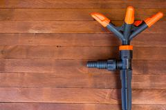 watering nozzle on a wooden table with copy space - stock photo
