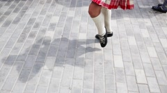 Legs of dancing woman in Scottish skirt and white stockings Stock Footage