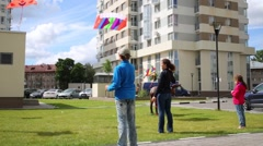 Woman, girl and boy launch colorful kites on wind among buildings Stock Footage