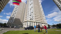 Woman, girl and boy launch kites on wind among buildings Arkistovideo