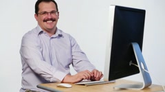 Happy man with mustache sits at table with computer and laughs Stock Footage